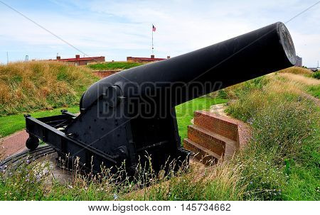 Baltimore Maryland - July 24 2013: One of the mighty military cannons mounted on swivel wheels atop an earthen rampart at Fort McHenry National Historic Park