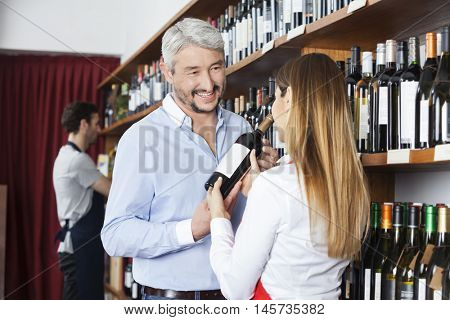 Customer Looking At Saleswoman Showing Red Wine Bottle
