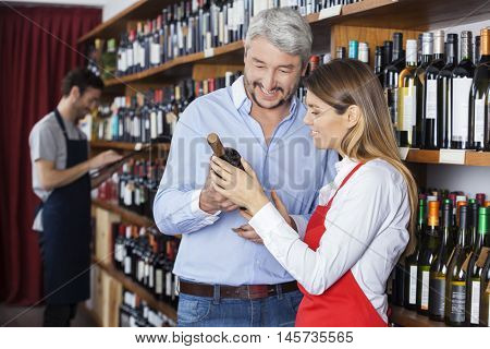 Saleswoman Showing Wine Bottle To Customer In Shop