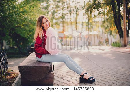Beautiful young woman in a pink skirt posing near wall with bright cotton candy summer warm evening