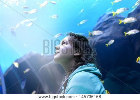 Young pretty caucasian woman with long curly brunette hair in green sweater watching fishes in a tropical aquarium tank with coral reef wild life at oceanarium.