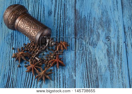 Spices mill with cinnamon and anise on blue