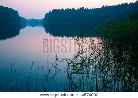 Dramatic sunrise over  quiet forest lake Seliger, Russia