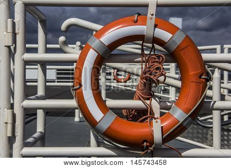 Orange lifebuoy attached to a railing of a pier
