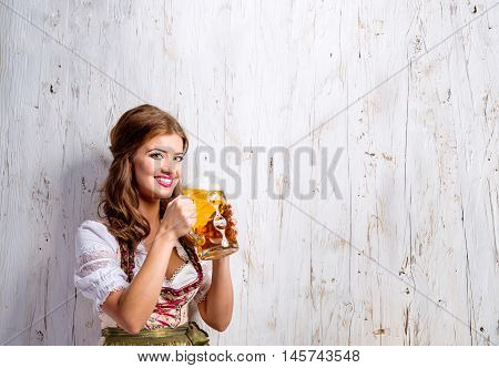 Beautiful young woman in traditional bavarian dress holding a mug of beer, drinking from it. Oktoberfest. Studio shot on white wooden background. Copy space.