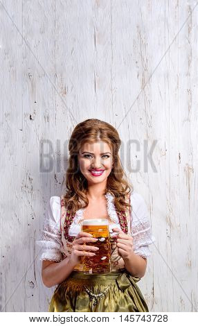 Beautiful young woman in traditional bavarian dress holding a mug of beer. Oktoberfest. Studio shot on white wooden background. Copy space.