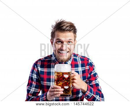 Handsome young hipster man in checked shirt holding a mug of beer, having foam on his upper lip. Oktoberfest. Studio shot on white background, isolated.