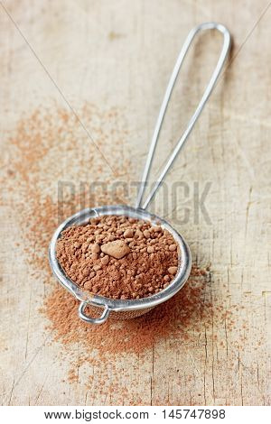 Cocoa powder in silver sieve on a rustic wooden board.
