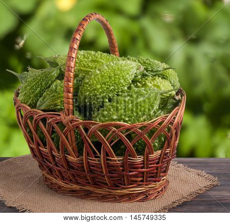 bitter melon or momordica in a wicker basket on a wooden table with a blurred background.