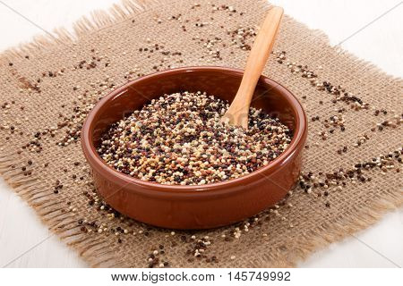 white red and black quinoa in brown earthenware bowl on jute