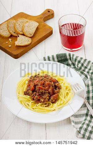 Pasta with sauce a bolognese from tomatoes and mincemeat on a white plate.