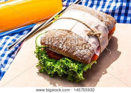 Picnic in the last days of summer: homemade sandwiches of whole grain ciabatta with ham, cheese and fresh vegetables and orange juice