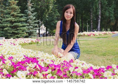 Pretty girl sits near the flowerbeds. Outdoor.