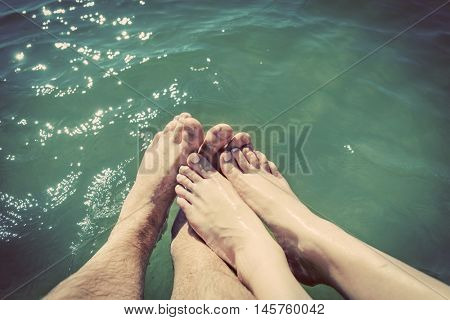 A couple in love wetting their feet in the sea. Summer holidays, romance. Vintage