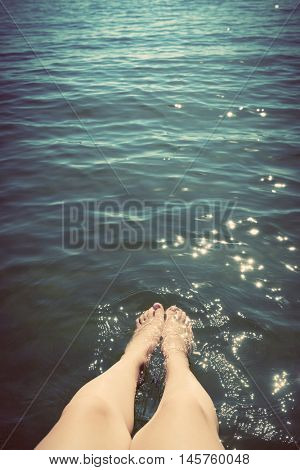Young woman wetting her legs in the sea. Summer holidays, freedom. Vintage