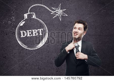 Debt concept with choking businessman and bomb sketch on concrete wall background