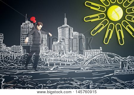 Abstract image of young businessman in suit pinned to dark background with city sketch and sun made of yellow clips and button magnet