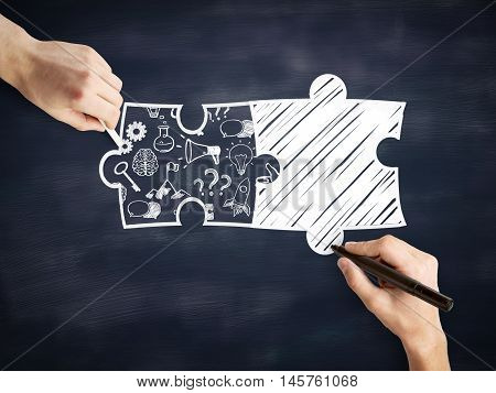 Male hands drawing puzzle pieces and success icons on blackboard background. Business partnership sketch