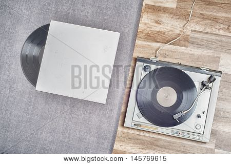 Old vinyl record in a paper case and turntable on the wooden floor