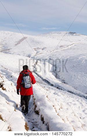 Indian woman hiking in winter snow Peak District UK