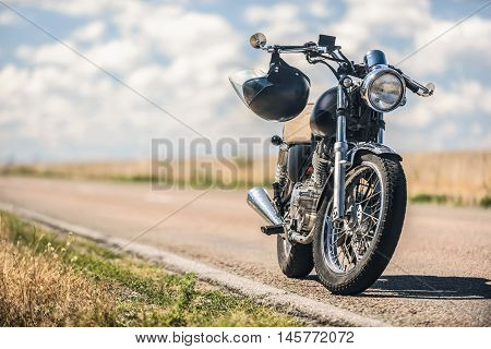 Time to trip. Cropped photo of black vintage motorcycle with helmet on handlebars parking on roadside