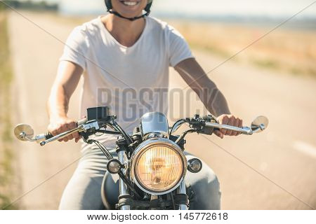 Let is go for joyride. Cropped photo of smiling man riding motorcycle on road, wearing black helmet and turning headlight