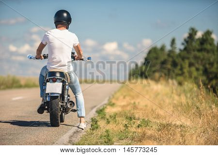 Exciting journey waiting for me. Rear view of guy wearing helmet and sitting on motorcycle, parking on roadside