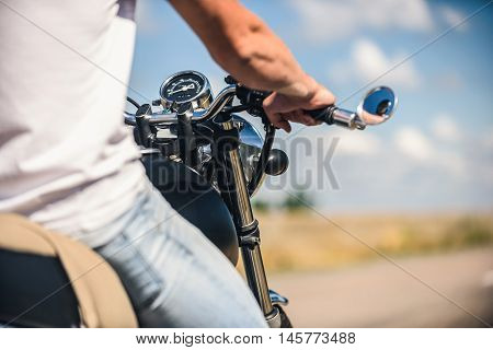 Loveto ride. Rear view of man sitting on motorcycle and holding handlebar with road in background