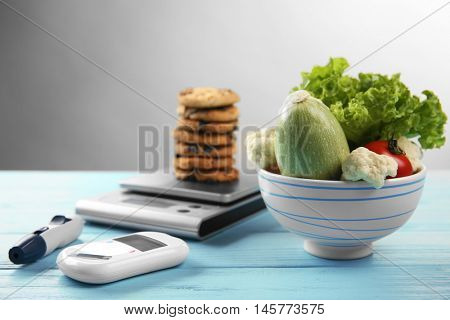 Glucose meter with vegetables and cookies on table