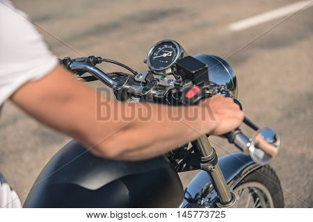 Faster, faster. Top view of man riding motorcycle on asphalt road, holding confidently handlebar by hands