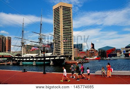 Baltimore Maryland - July 22 2013: The World Trade Center Tower designed by I. M. Pei and the 1853 U. S. S. Constitution tall ship at Inner Harbor