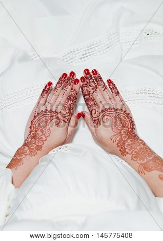 Girl is holding hands with henna tattos on white dress