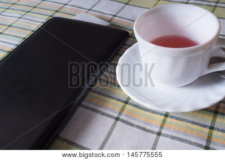 Standing on the table white Cup of tea and a black folder with the receipt for payment