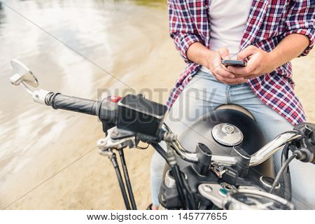 Important to be always connected. Close up of guy writing message on mobile phone, sitting on his motorcycle near water