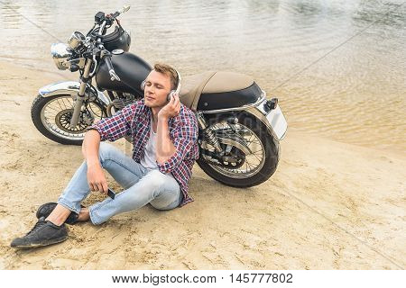 Time to relax with music. Top view of young man listening to music on headphones and sitting outdoor with his motorcycle in background