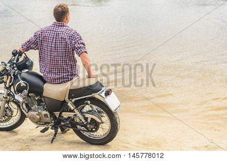Spending day with his bike. Croppead shot of rear view man sitting on his vintage bike by lake and looking forward