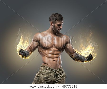 Handsome power athletic man bodybuilder. Fitness muscular body on dark background.