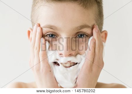 Smiling Young Boy Applying Shaving Cream To Face