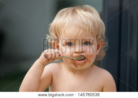 Funny blond baby eating chocolate with a spoon