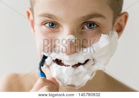 Smiling Boy Shaving Face With Plastic Razor