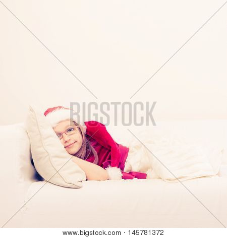 Girl family time during christmas. Cute little lady crawling on sofa. Small woman lying on the couch. Resting time wearing red santa claus hat and shoes.