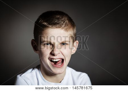 Solitary Boy Making Faces Against Black Background