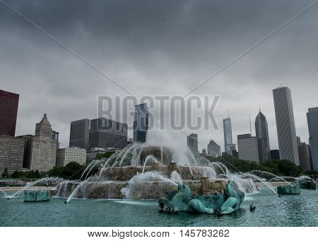 Chicago United States: May 27 2016: Buckingham fountain with skyline on cloudy day. After a long wait for restoration the fountain is running during daytime hours.