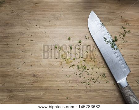 Chopped up Dill remains and a knife on a wooden cutting board.