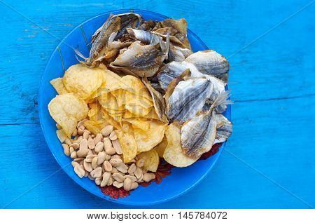 Close up of the mix beer snacks on wooden background. Potato chips roasted and salted peanuts dried fish in blue plate on the blue wood background.Top view