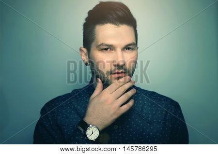 Handsome hipster man in blue jeans shirt and classic watch over grey studio background looking questionably and thoughtfully.