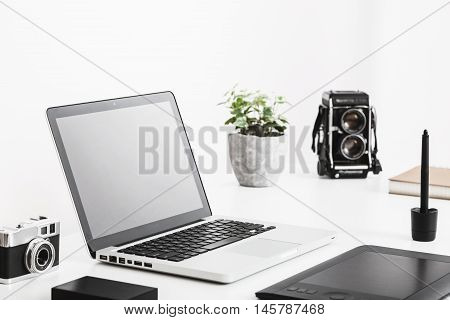 Photographer's desk with laptop, vintage camera and tablet. Modern and retro technology. White background.