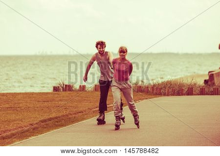 Relax leisure love romance dating sport fitness concept. Boy chasing his girlfriend. Couple spending time together skating on rollerskates.