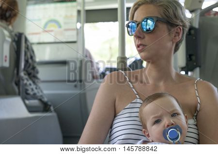 Mother with her baby boy over her legs on urban bus