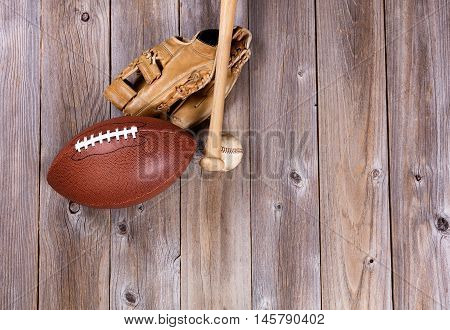 Overhead view of baseball and football equipment on rustic wooden boards.
